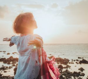 girl standing on edge of ocean with her arms out and sun behind eher
