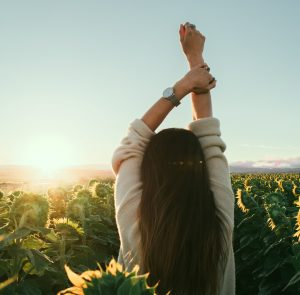 woman standing in field of sunflowers holding her hands up into the sky